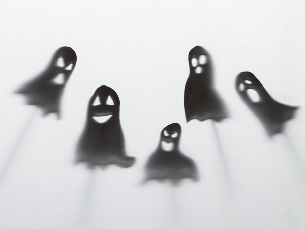 Black Halloween silhouettes of ghosts and poltergeist on white background