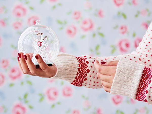 Woman holding angel globe