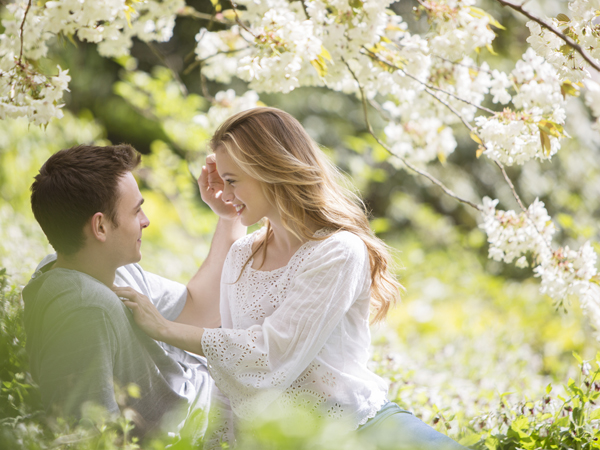 Couple relaxing in grass under tree with white blossoms