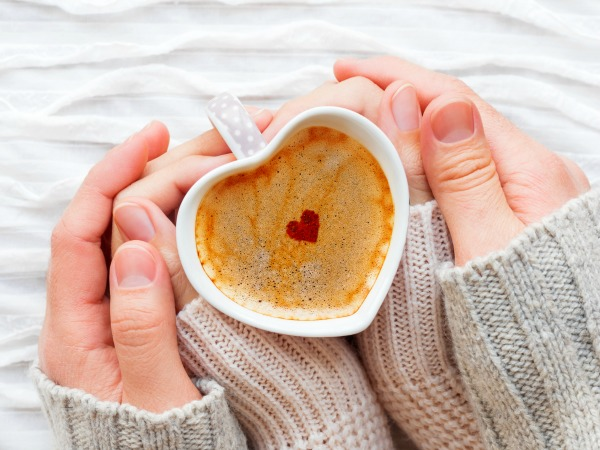 Woman and man holds a cup of hot coffee with cinnamon heart. Winter and Valentine's Day fabric background with sparkling silver and red confetti.