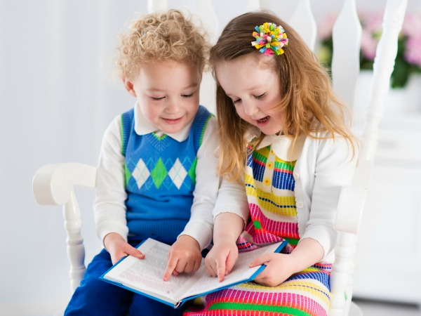 Kids read a book. Children reading books in white chair. Toddler kid and preschooler child doing homework. Little boy and girl study at home after kindergarten. Brother and sister play and laugh.