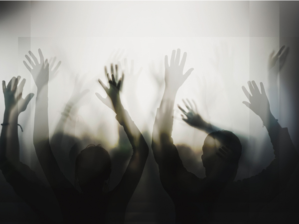 Silhouette of people with raised hands