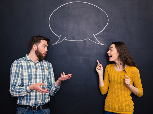 Beautiful couple talking over blackboard background with speech bubble