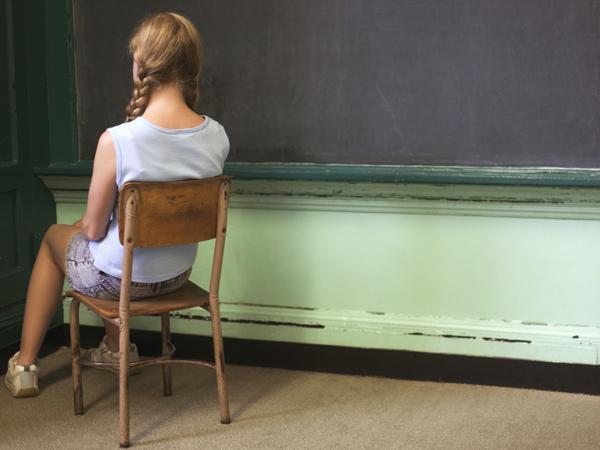 Girl sitting in corner facing wall