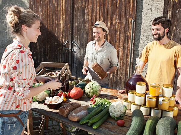 Woman buying organic produce at stall