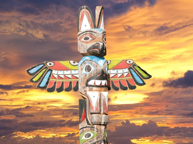 Isolated totem wood pole in the gold sunset background