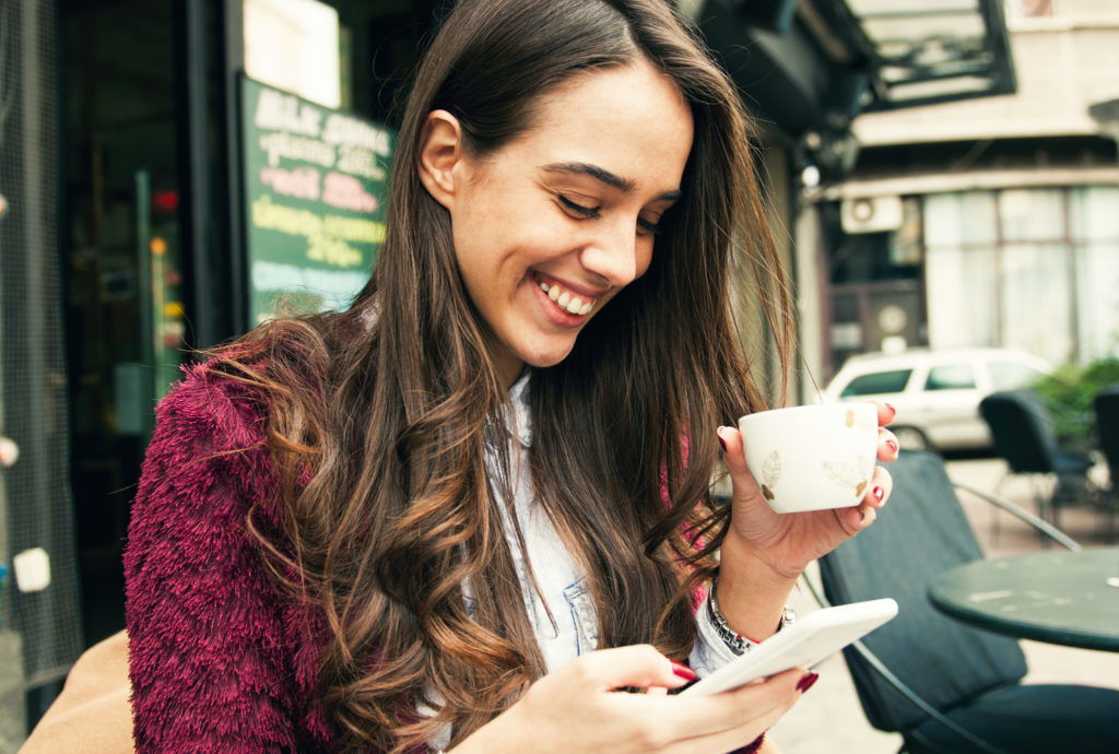 Young smiling woman using smart phone while drinking coffee