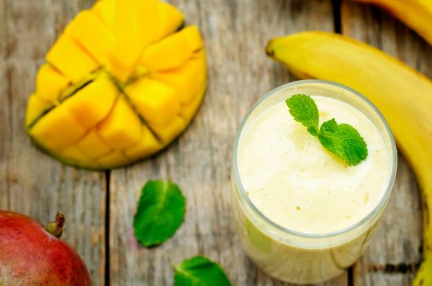 banana mango smoothies on a dark wood background. the toning. selective focus