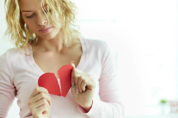 Sad female tearing up red broken paper heart
