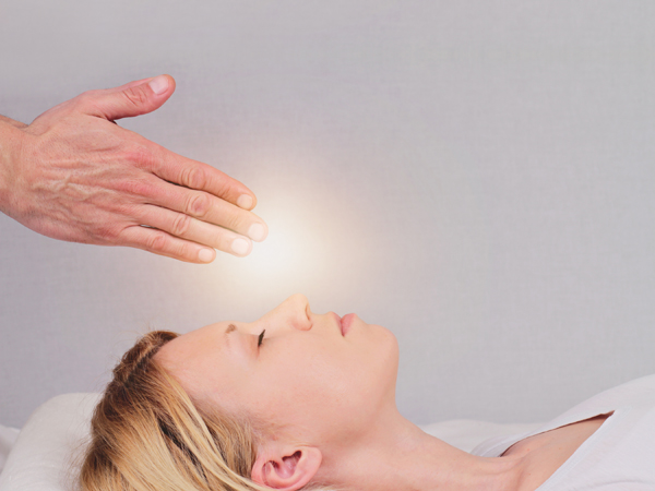 Attractive young woman having reiki healing treatment