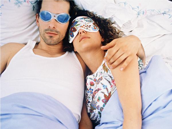 Couple sleeping in bed, wearing sleep masks