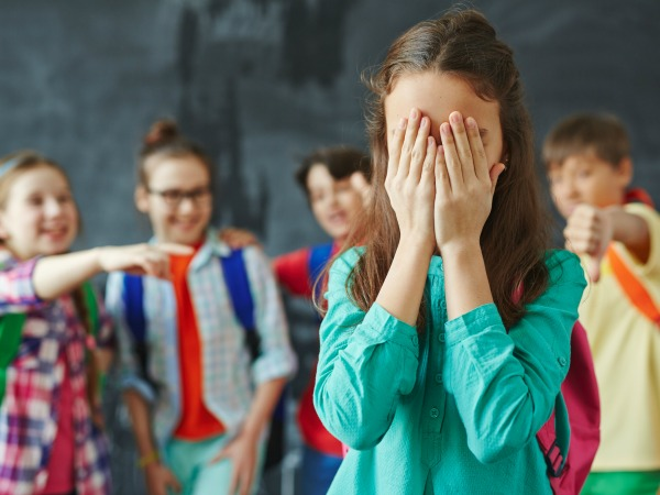 Schoolgirl hiding her face in palms on background of teasing classmates