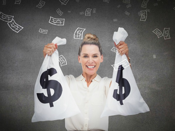 Smiling businesswoman holding cash bags