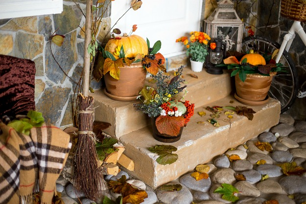 autumn scenery indoors. An arch with dry leaves, pumpkins, a mountain ash