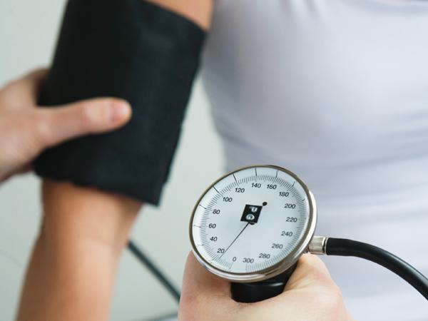 Hands using blood pressure cuff