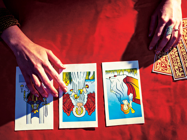48751609 - overhead view of cropped hands with tarot cards on table