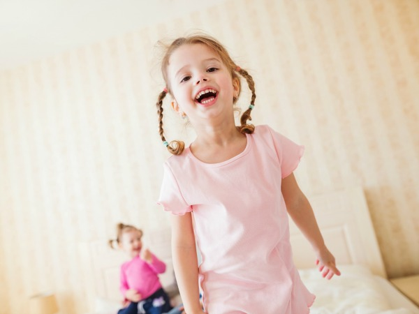 Two cute little girls in bedroom jumping on a bed