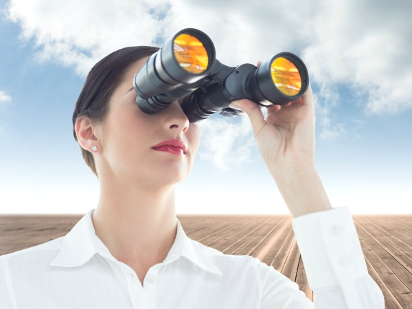 Business woman looking through binoculars against cloudy sky background