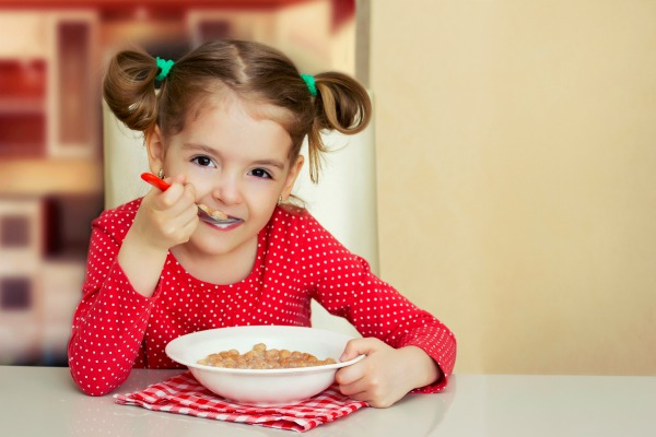 Little girl sitting at the table and eating milk snack. Happy child have a breakfast. Kids nutrition background.