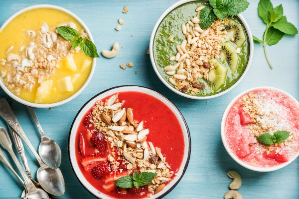 Healthy summer breakfast concept. Colorful fruit smoothie bowls with nuts and oat granola on turquoise blue background . Yellow, red, green, pink. Top view, horizontal