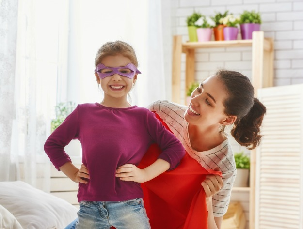 Happy family is preparing for a costume party. Mother and her child girl playing together. Girl in Superman's costume.