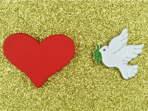Red love heart with white dove of peace carrying olive branch on a sparkling gold glitter background.
