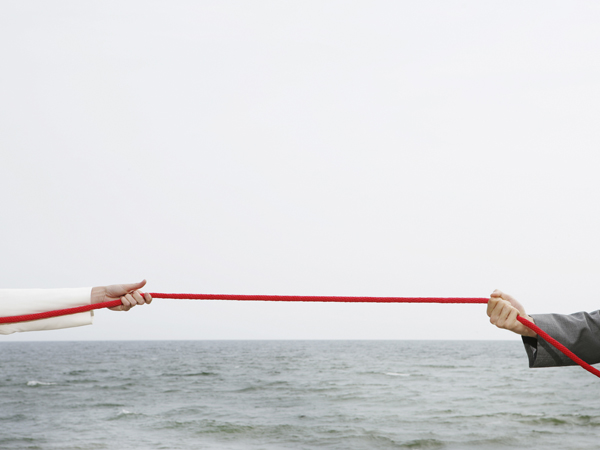 Close-up of red rope being pulled in both directions, with ocean in background