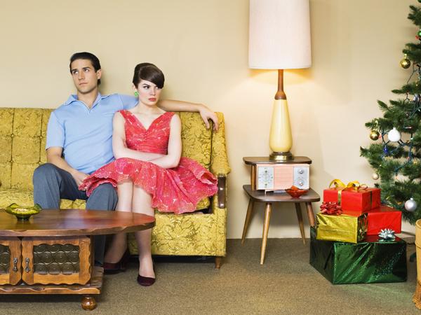 upset looking couple next to christmas tree