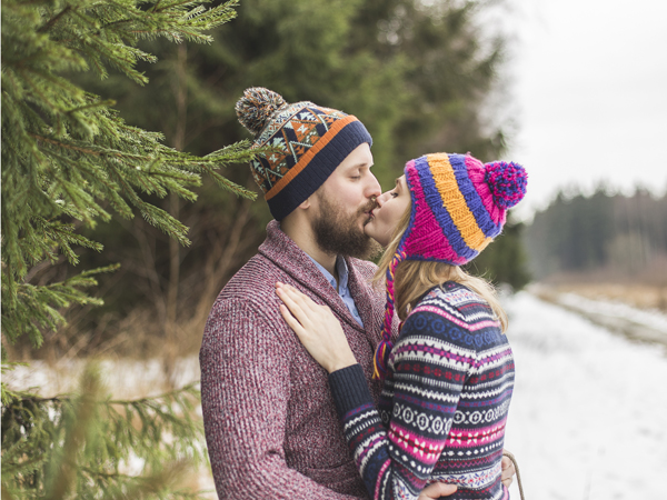 Christmas love couple walks in the wood in colorfull clothes