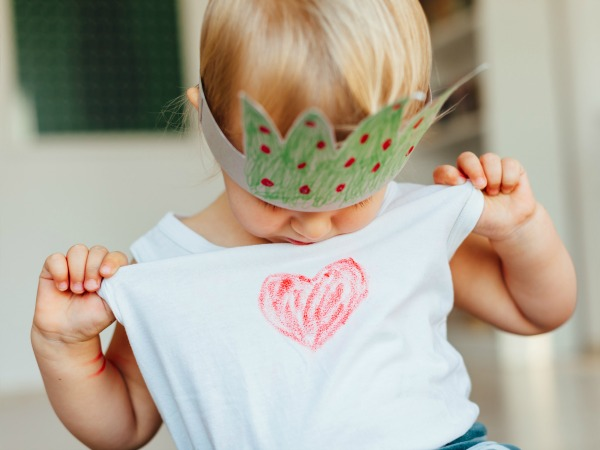 Little girl looking at heart on your shirt