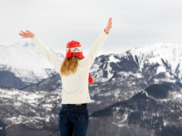 winter scene: blond girl on the top of a mountain. Copy space on the upper side