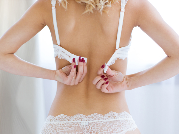 Rear view portrait of a sexy woman unbuttoning brassiere