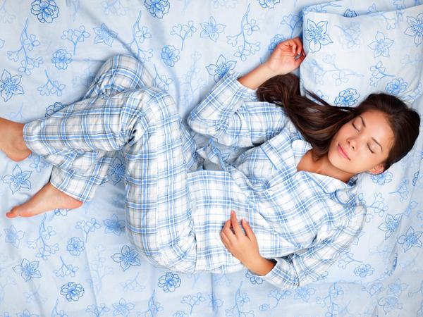 Sleep. Woman sleeping in bed having beauty sleep in pajamas. Beautiful cute girl in her twenties. Asian Caucasian female model in full body lying down.