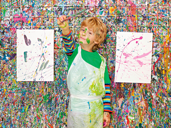 Boy in front of paint splattered wall